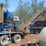 Forest harvest debris being transported and processed for use as substrate